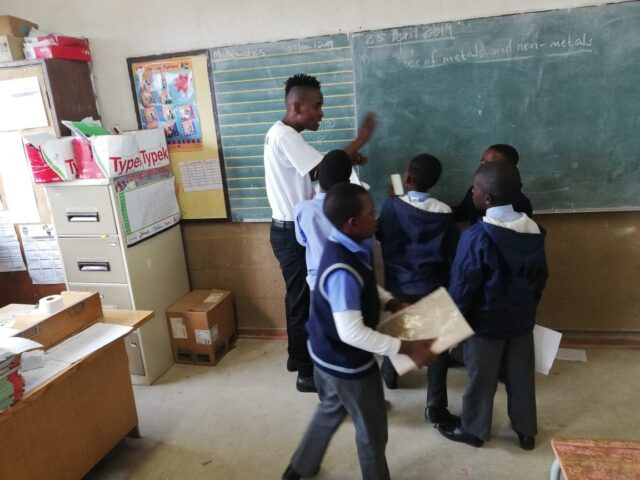 Service leader at a chalkboard instructing several learners