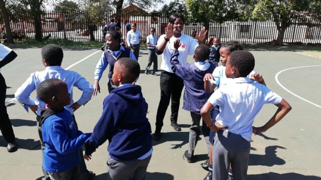 Service leader on the playground with children, high-fiving one of them