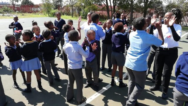 Learners on the playground high-fiving each other and service leaders