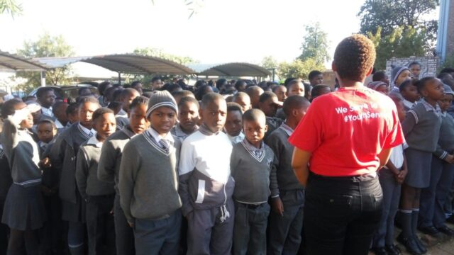 Service leader stands in front of a group of children
