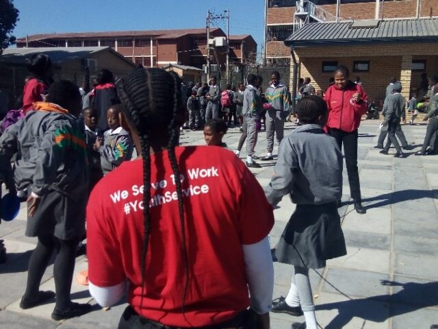 Service leader on the playground with learners