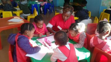 Service leader providing homework help at a table with young learners