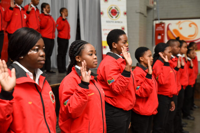 Service leaders in red jackets with their hands up to take the City Year pledge