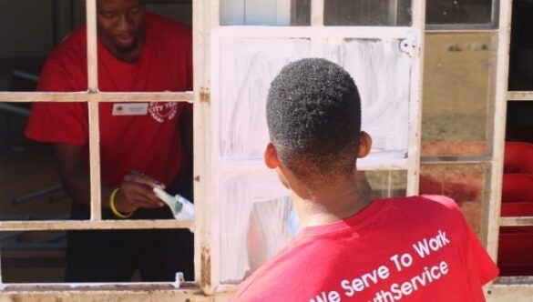 Service leaders painting a window pane