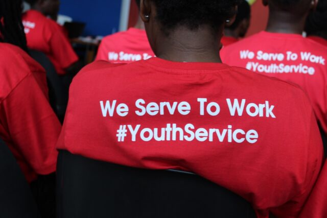 Red t-shirt that reads: We Serve To Work #YouthService