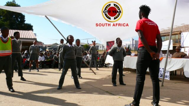 Service leader with learners under a tent that says City Year South Africa