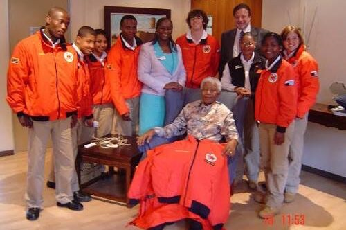 City Year South Africa service leaders surrounding President Mandela with a red jacket on his lap