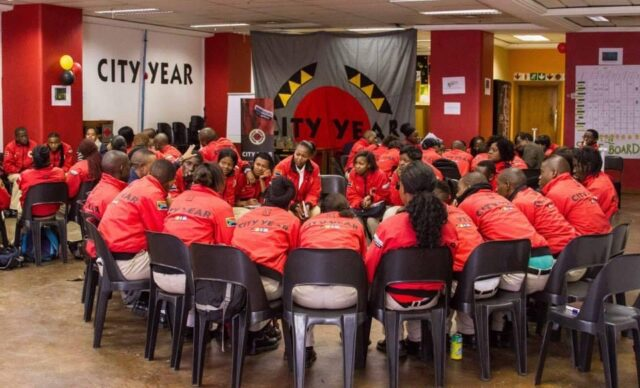 Group of City Year service leaders in red jackets sitting in a circle in training