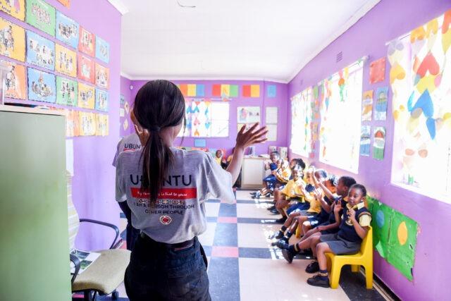 Female service leader greeting a classroom of children in an Ubuntu shirt