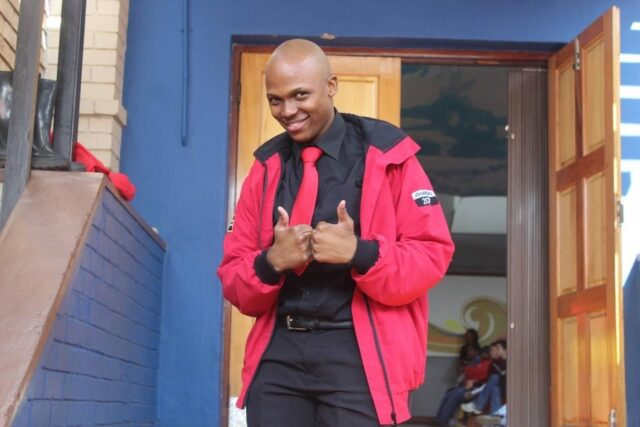 Esau in his red jacket giving two thumbs up and smiling